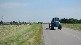 Tractor drive on rural road and agriculture field of straw bales stock video footage