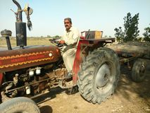 A tractor driver driving his tractor stock images