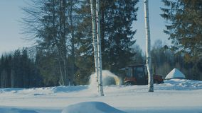 Tractor driving backwards and removing snow from the winter road near terem. 4K stock footage
