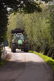 Tractor driving on country road Royalty Free Stock Image