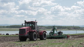 Tractor driving on a countryside road in field near a lake stock video footage