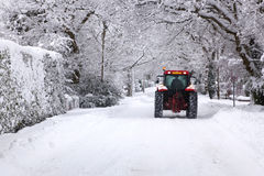 Tractor driving down a snow covered road. A red tractor driving down a snow covered UK road during a winter snowfall in January Stock Image
