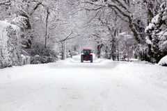Tractor driving down a snow covered road. A red tractor driving down a snow covered UK road during the winter snowfall winter in January 2010 Stock Photography