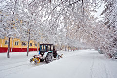 Tractor driving down a snow covered road during the winter snowfall winter in Siberia Royalty Free Stock Images