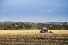 Tractor driving in field, autumn rural landscape Royalty Free Stock Photography