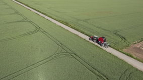 Tractor driving on a small countryside road,aerial view stock video footage