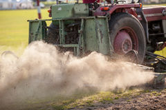 Tractor in dust. A Tractor produce dust during while harvesting Royalty Free Stock Photography