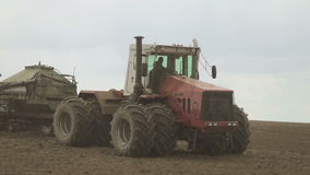 Tractor with eight wheels and a trailed hopper for grain on field. stock video