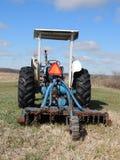 Tractor en campo de la primavera con el vehículo de movimiento lento e Imagenes de archivo