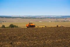 Tractor en el campo de la cosecha limpia del trigo Fotografía de archivo
