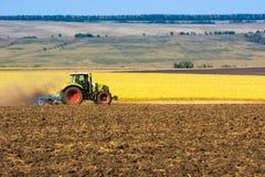 Tractor en el campo de la cosecha limpia del trigo Foto de archivo libre de regalías