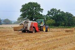 Tractor en het In balen verpakken Machine Stock Afbeelding