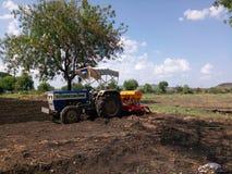 Tractor en las granjas con las colinas de los árboles del fondo y cielo azul y campo agradables imagen de archivo libre de regalías