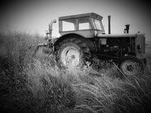Tractor en un campo de blanco y negro admitida del trigo Foto de archivo