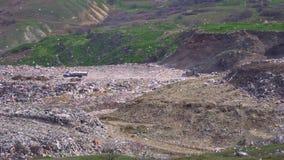 Tractor en vrachtwagen bij een reusachtige giftige stortplaats stock footage