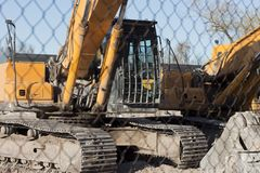 Construction machines placed on the site. Tractor equipment placed on the construction site behind the fence stock images