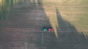 Tractor in evening spraying autumn crop field with sprouts, aerial stock video footage