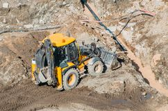 Tractor excavator with bucket rides running through mud lands setting, view from the height. Stock Image