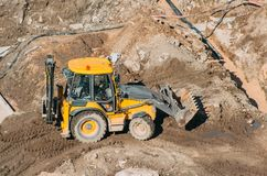Tractor excavator with bucket rides running through mud lands setting, view from the height. Royalty Free Stock Images