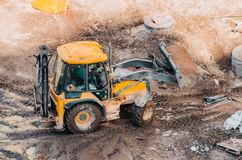 Tractor excavator with bucket rides running through mud lands setting, view from the height. Stock Photos