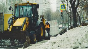 Tractor excavator digging the ground, standing next to the worker stock footage