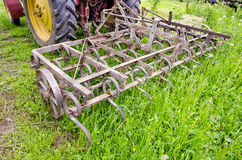 Tractor on farm field gras with metal harrow Stock Images