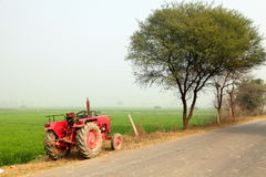 Tractor & Farm Land. A tractor is on countryside landscape Royalty Free Stock Image