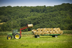 Tractor on farm loading bales in hay onto trailer Stock Images