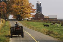 Tractor on farm road with barn and silo in background in autumn, VT Royalty Free Stock Photos