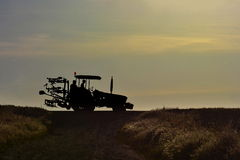 Tractor with farmers silhouettes go home in sunset Stock Images
