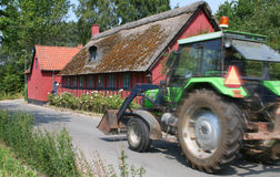 Tractor and farmhouse. Side view of green tractor with red farmhouse building in background stock photos