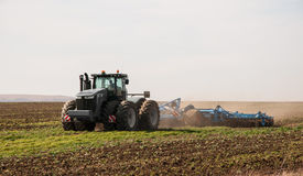 Tractor farming. Tractor ploughing field in spring royalty free stock photography