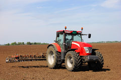 Tractor on a farmland. Red tractor on a farmland on a sunny day Stock Image