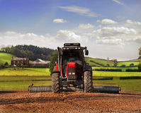 Tractor on Farmland, Somerset. A tractor ploughing the dirt in Rural Somerset UK, with landscape and farmhouse in the background stock photos