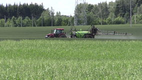 Tractor fertilize crop field at herbicides, pesticides. Panning stock footage