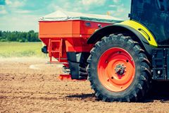 Tractor fertilize the field with granular fertilizer. On sunny summer day stock photo