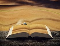 Tractor fertilize the field on the pages of book