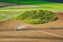 Tractor fertilize a field. Tractor fertilize a spring field before the seeding. Ukrainian valley, Europe royalty free stock photography