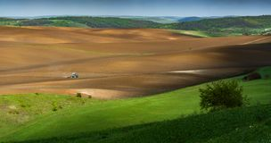 Tractor fertilize a spring field before the seeding. Ukrainian valley, Europe royalty free stock images
