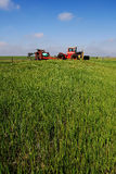 Tractor and Fertilizer. In field at side of the country road in spring stock images