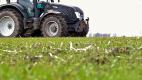 Tractor and fertilizer. Tractor scatters fertilizer in the field of the young wheat,slow motion video clip stock video