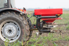 Tractor and fertilizer. Spreader in field Stock Photo
