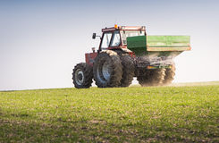 Tractor and fertilizer. Spreader in field royalty free stock photos