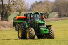 Tractor and fertilizer spreader in field. A modern john deere tractor spreading fertilizer pesticides in crop field with Amazone spreader stock photography