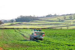 Tractor and fertilizer spreader in field Stock Images