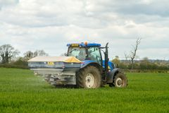 Tractor and fertilizer spreader in field Stock Image
