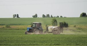 Tractor With Fertilizer Spreader Spraying Pesticides Or Chemicals On Field With Sprayer At Spring. Season stock footage
