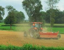 A tractor fertilizing a field stock images