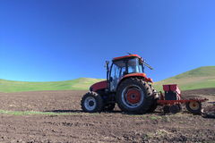 Tractor on field. A tractor on field with green mountain and blue sky Stock Photos