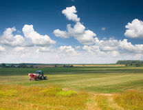 Tractor in the field. Under clouds Royalty Free Stock Images